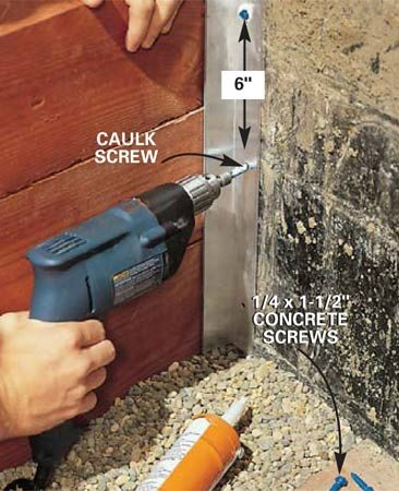 <b>Photo 13: Drive concrete screws</b></br> Apply a dab of caulk to 1/4-in. x 1-1/2 in. concrete screws and drive them home. Do not secure the stop to the timber wall. This allows the timbers to move slightly during freeze/thaw cycles.