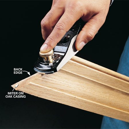 <b>Photo 3: Tighten miter joints</b></br> Tighten miters by trimming excess with a sharp block plane. Work from the short side to the long side of the miter to avoid planing against the grain. Angle the plane slightly to the backside of the miter to help the face of the miter fit tighter.