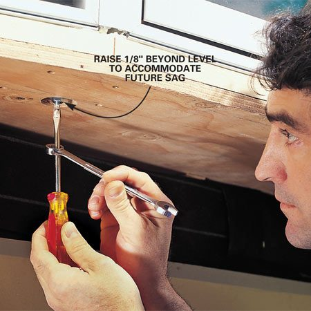 <b>Photo 10: Level the footboard by turning the adjustment nut. </b></br> Tighten the adjustment nut on the bottom until the footboard is level or slants slightly upward (about 1/8 in.), to compensate for cable stretch. Do it right; once the bottom of the window is insulated and sheathed, the nuts will be inaccessible.