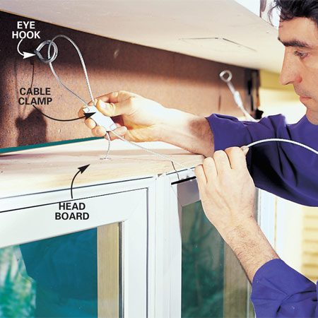 <b>Photo 9: Hold the window in place with support cables. </b></br> Use cable clamps to tighten the support cables around eye hooks screwed firmly into the header. If space over the window is limited (our manufacturer wanted a minimum 30-degree cable angle), secure the cables to eye hooks screwed into the overhanging rafter tails or blocking nailed between the tails.