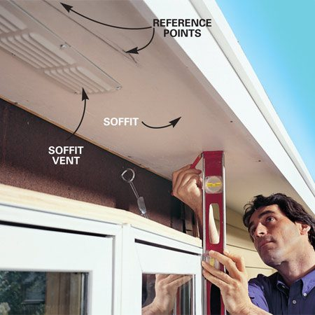 <b>Photo 12: Mark the window profile on the soffit. </b><br/>Use a level to transfer the profile of the window up to the soffit, then make marks 1/2 in. back and secure 1x2 cleats to those marks. Add fiberglass insulation to the cavity. If the distance from window top to soffit is less than 6 in., you can enclose the top with the same metal flashing shown in Photo 15.