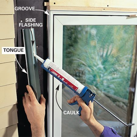 <b>Photo 14: Caulk and install the flashing. </b><br/>Apply caulk to the back of the side flashing, then tap the tongue of the flashing into the groove of the window. Prevent damage to flashings by hammering against a wood scrap.