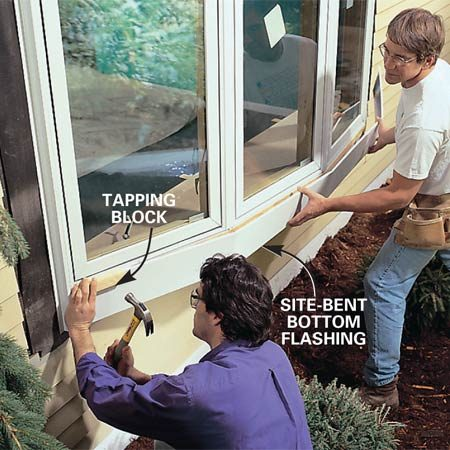 <b>Photo 15: Set the bottom flashing in place.</b><br/>Install the bottom flashing. First hold the flashing in place, mark the corners and lightly pre-bend the flashing to accommodate the profile of the window. Secure it into the bottom groove of the window using a tapping block. Caulk the seam between the bottom and side flashings.