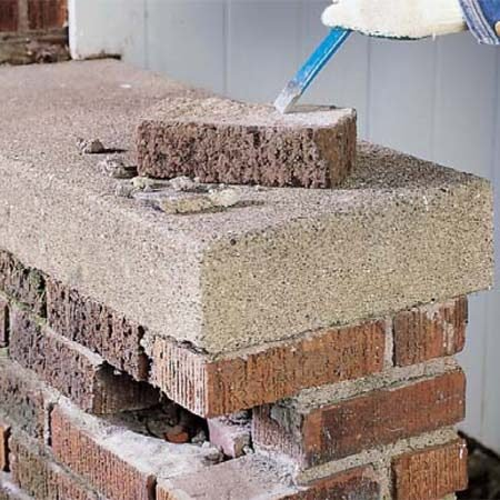 <b>Photo 2: Clean the brick</b></br> Knock the mortar off the old brick by holding the chisel at a high angle and hitting it with rapid, light blows while moving the chisel tip quickly over the surface of the hardened mortar. Clean the brick with a wire brush and rinse it off with water.