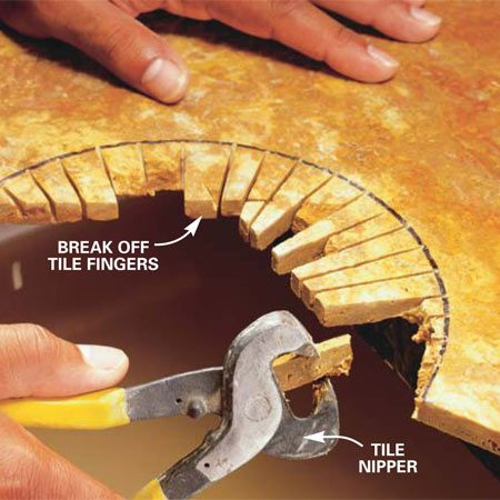 <b>Photo 6: Break off the sections</b></br> Snap off the sawed sections with a tile nipper or by tapping each with the handle of a screwdriver or trowel.
