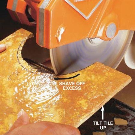 <b>Photo 7: Clean the edge</b></br> Tilt up the front edge of the tile and clean up the cut by shaving away the excess. Remove no more than 1/16 in. at a time.
