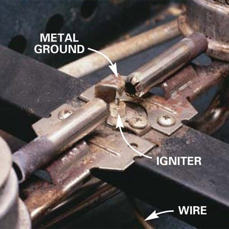 <b>Photo 3: Look for the igniter (spark ignition)</b></br> Identify a spark ignition (igniter) range by a little ceramic nub located between two burners. Look for wires running to it. The igniters on sealed burner ranges are alongside the burners.