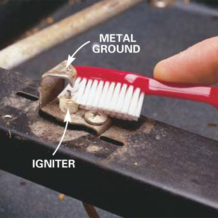 "<b>Photo 4: Clean the igniter</b></br> <p>Brush away gunk around and on the igniter with an old toothbrush. It's common for  food that has boiled over to build up here. Clean the metal ""ground"" above the igniter wire, too. It must be clean to conduct a spark. Close the lid and turn  the burner knob to ""Light"" to test the burner. </p>"
