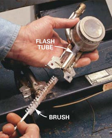 <b>Photo 2: Brush out the tube</b></br> Shove the brush into the flash tube to clear gunk and dust. Although some pros use water and degreasers to clean the burner assembly, we don't recommend them because they could cause rust.