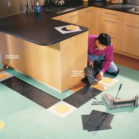 <b>Photo 10: Lay the border</b><br/>Lay the border starting with full tile. Mark and cut partial tile to complete each section. Continue to measure and cut tiles to fill the space between the black border and the walls and cabinets.