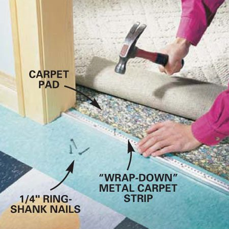 <b>Photo 11: Install carpet strip</b><br/>Nail a wrap-down metal carpet strip over the tile at doorways to carpeted rooms. Push the carpet to the back of the strip with a putty knife and trim it flush with a sharp utility knife. Use a hammer and block of wood to bend the metal down and pinch the carpet.