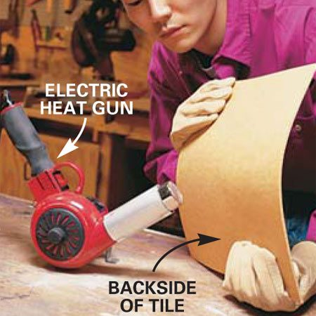 "<b>Photo 12: Prepare tile for cutting circles</b></br> Draw a circle on the face of a tile with a compass. (Use a few layers of masking tape to protect the tile at the pivot point; see Photo 13). Heat the tile from the backside with a heat gun set on ""high."" Keep the tile moving over the heat source until it's flexible (about 60 seconds). Wear leather gloves to protect your hands from burns."