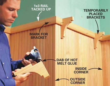 <b>Photo 15: Fit the rail and brackets </b></br> Cut 1x3 boards to fit on top of the paneling and drill two 3/32-in. pilot holes at each stud location. Temporarily fasten them and position the brackets. Attach them temporarily with a pea-size dab of hot melt glue. Stand back and look. Adjust the bracket locations if you like. Then mark the location of each bracket. Remove the brackets and 1x3s.