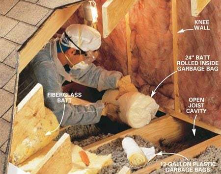 <b>Photo 4: Plug open joist spaces</b></br> Plug all open joist spaces under insulated side walls. Cut a 24-in. long piece from a batt of fiberglass insulation and place it at the bottom of a 13-gallon plastic garbage bag. Fold the bag over and stuff it into the joist space under the wall.