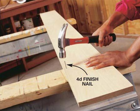 <b>Photo 1: Secure the board </b></br> Secure the board for cutting lengthwise by nailing it to sawhorses. Position one finish nail at each end near the edge of the board and away from the path of the blade. Pound the nails flush to the surface.