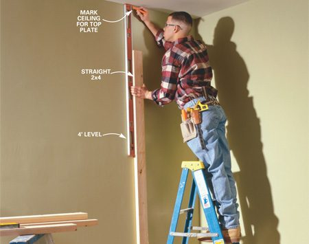 <b>Photo 3: Mark the top plate position</b><br/>PLUMB  up from the bottom plates with a straight 2x4 and 4-ft. level and mark the top  plate location on the ceiling. Snap chalk lines between the marks. Locate the  ceiling joists with a stud finder or by rapping with your knuckle, then mark  them where they cross the top plate. Our ceiling joists run parallel to our new  wall.