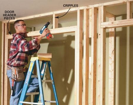 <b>Photo 6: Install the headers</b><br/>NAIL together the 2x4 headers with 16d nails, set them on top of the trimmers, and nail them to the studs. Cut and toe-screw the cripples to the top plate and header.
