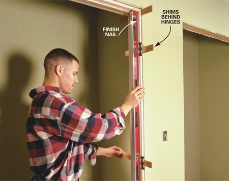 <b>Photo 8: Shim the side jamb until plumb and nail</b></br> DRIVE one 8d finish nail through the jambs and shims at the top on each side. Set a 4-ft. level on one jamb and plumb it by sliding pairs of shims behind each hinge and at the bottom of the jamb. Drive one finish nail into each set of shims. Double-check for plumb and adjust by tapping shims in or out.