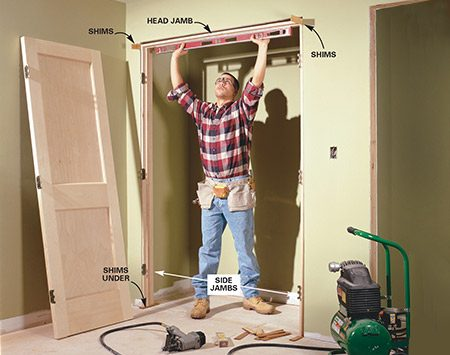 <b>Photo 7: Level the door jamb</b></br> CENTER the door jamb in the opening and wedge it tight by sliding in a pair of shims at each top corner. Set a 4-ft. level against the head jamb to check for level.