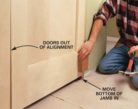 <b>Photo 11: Fine tune the fit</b></br> ALIGN the door bottoms by tapping the door jambs slightly in or out until they're even. Use a block of wood and firm hammer blows. Then drive in additional nails to secure the jamb in the new location.
