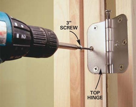 <b>Photo 12: Strengthen the hinges</b></br> REPLACE the center screw in the jamb half of the top hinges with a 3-in. screw the same or a similar color. Drive the screw through the jamb and into the 2x4 door framing to add extra support and keep the door from sagging over time. Double-check the space between the doors and add a shim if necessary.