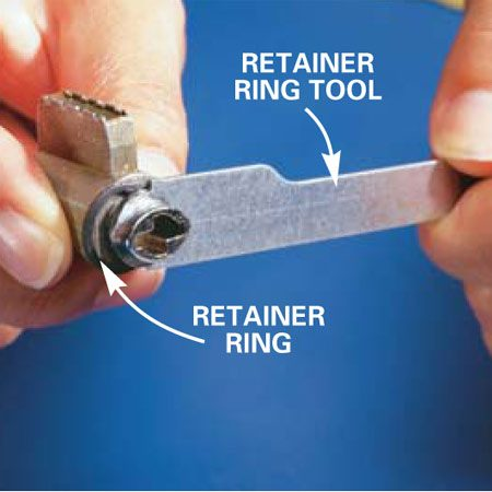 <b>Photo 3: Remove the retainer ring. </b></br> Push the retainer ring tool against the retainer ring to pop it off the cylinder.