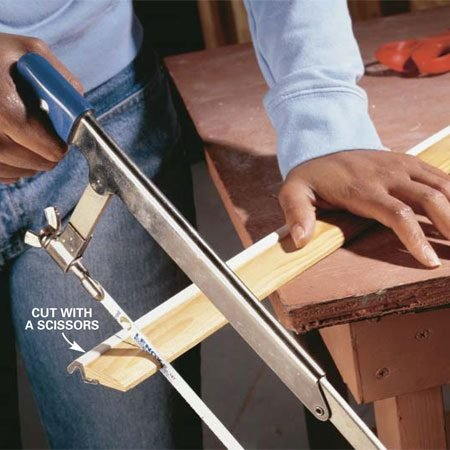 <b>Photo 3: Cut the top piece</b></br> <p>Cut the foam part of the weatherstripping with a sharp scissors. Then cut the wood flange with a hacksaw or other fine-tooth saw.</p>