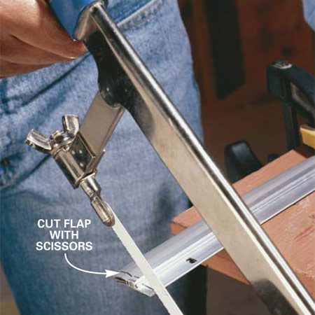 <b>Photo 9: Cut the door sweep</b></br> <p>Cut the flexible flap with a sharp scissors or sharp utility knife. Then cut the flange with a hacksaw.</p>