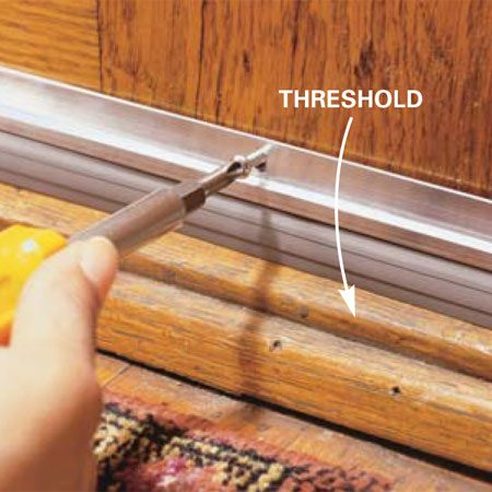 <b>Photo 11:   Attach the sweep</b></br> <p>Push the sweep down against the threshold and drive the screws. Open and close the door to test the seal.</p>