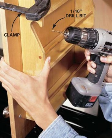 <b>Photo 4: Attach the rack to the door </b></br> Clamp the finished rack to the door, then drill angled pilot holes through the rack and into the door every 8 in. Secure with brad nails (remove the door for this step if you find you need a more solid surface for hammering). Use carpenter's glue for a more permanent installation.