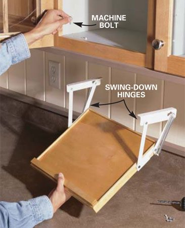 <b>Photo 3: Install the rack on the cabinet </b></br> Mount the hinges to your base using wood screws. Hold the assembled unit in position under the cabinet, then mark the holes for the brackets (a two-person job). Drill the holes, then secure the brackets to the cabinet using short machine screws, washers and nuts.