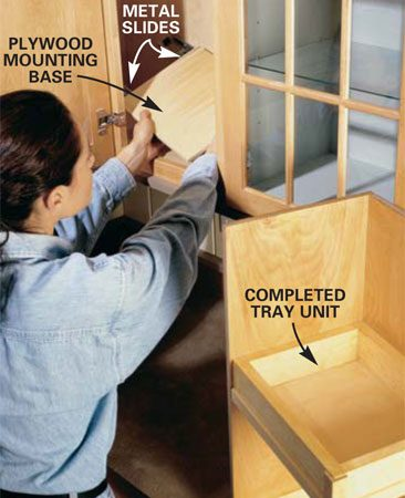 <b>Photo 3: Place the base in the shelf opening. </b></br> Cut the mounting base plywood slightly smaller than the other tray bottoms, then secure the two slides parallel to each other about 1 in. from each edge. Slip this mounting base into the opening, extend the slides, then screw them to the cabinet bottom at the rear of the cabinet. Install the slides parallel to the cabinet sides, so the base slides back and forth freely.