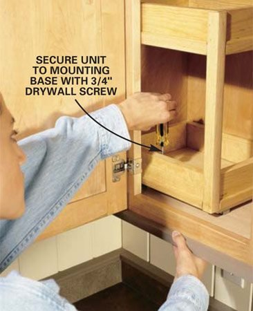 <b>Photo 4: Attach the tray unit to the mounting base.</b></br> Screw the tray unit to the mounting base using 3/4-in. screws. After installing the first screw, slide the unit forward and back, then adjust it until it runs parallel to the cabinet sides and install three more screws.