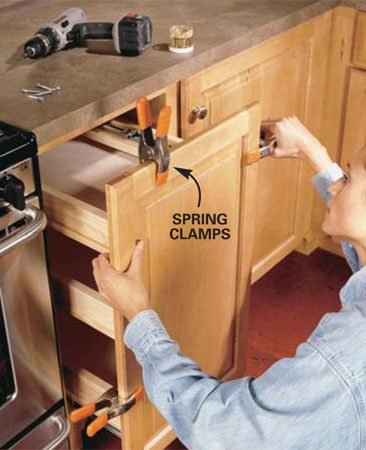 <b>Photo 6: Attach the cabinet door. </b></br> Clamp the cabinet door to the front of the pantry assembly; center it and make the height even with adjacent doors. Pre-drill eight holes through the plywood upright and drive screws into the back of the cabinet door. After installing two screws, close the door to check its alignment with the adjacent doors. Make adjustments, then install the remaining screws. Use short screws so they don't penetrate the front of the cabinet door (duh!).