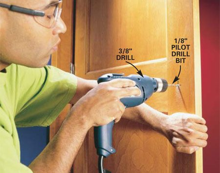 <b>Photo 1: First bore a pilot hole</b></br> Mark the center of the hole and drill a 1/8-in. pilot hole completely through the door to transfer the center to the other side. Keep bit level and square to door.