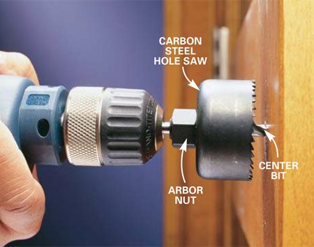 <b>Photo 2: Align bit for full contact</b></br> Align the center bit with the pilot hole. Grab the drill firmly with both hands and press straight in. Run the drill slowly and adjust the angle until the hole saw teeth are contacting the wood evenly.