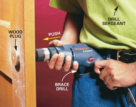 <b>Photo 4: Finish the hole from the other side</b></br> Align the center bit with the pilot hole on the opposite side of the door and complete the hole. Brace the drill against your hip for extra power and better control. The wood plug will stick in the saw and pop out the other side.