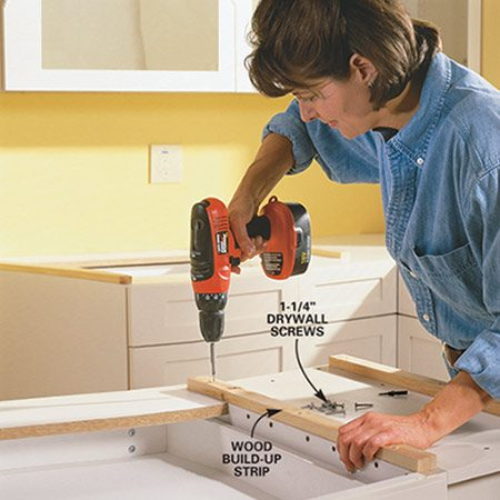 <b>Photo 2: Attach the build-up strips</b></br> Screw the build-up strips to the tops of your cabinets (sides and along the back) using 1-1/4 in. drywall screws. You may not need them on the cabinet end where the manufacturer has installed a finished end.