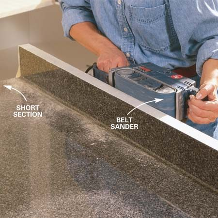 "<b>Photo 7: Sand to the scribe line</b></br> Belt sand to your scribe line using an 80-grit belt. Make sure the top is clamped down to your work surface to keep it from ""walking"" away from you as you sand. Sand only to your scribe line, keeping the belt sander at 90 degrees or more to the top of the backsplash as shown. Reposition the top and rescribe and sand if necessary."
