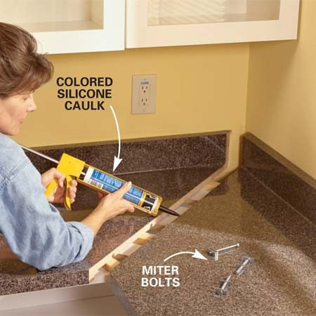 <b>Photo 13: Caulk the miter joint</b></br> Squeeze a bead of silicone adhesive caulk onto the edge of each miter joint and then fasten the countertop sections together as before. Be sure the tops are flush as you tighten the bolts.
