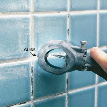 <b>Photo 1: Grind out the grout</b></br> Attach the removal unit and set the bit depth to 1/4 in. Run the tool guides between the tiles and grind through the old grout. Clean joints with a grout saw.