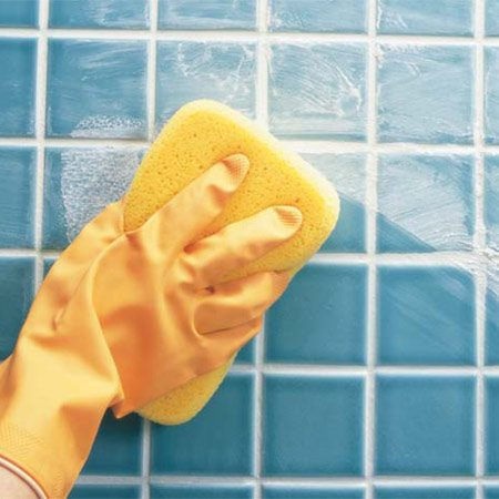 <b>Photo 3: Wipe off excess</b></br> Wipe the excess grout and film off the face of the tile with a damp sponge, rinsing it often.