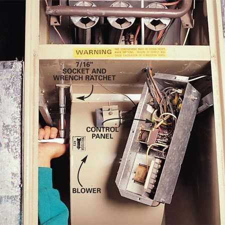 <b>Remove the bolts that secure the blower</b></br> <p>Remove the blower (also called a squirrel cage) in order to   clean it. If you have a control panel in front of the blower,   two screws will loosen it and you can let it hang. Next, using a   7/16-in. socket and ratchet, remove the two bolts that hold the   blower in place, then gently  lift it out. </p>