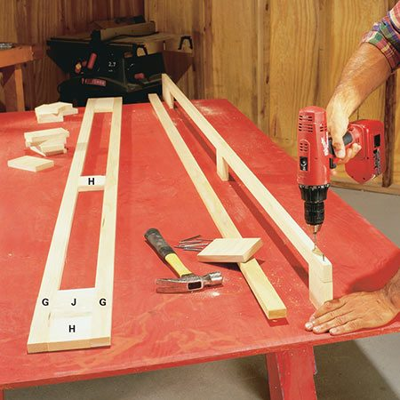 <b>Photo 6: Build the partition faces</b></br> <p>Cut the long stiles (G) of the face frame and nail them with 8d finish nails to the short rails (H and J). Use a drill bit to make a pilot hole slightly smaller than the diameter of the nail. Set the nails and fill the recesses with matching putty later.</p>