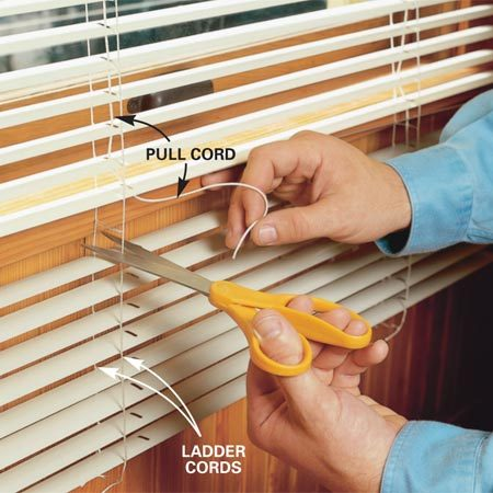 <b>Photo 2: Remove pull cord</b></br> Extract the pull cord from the center of the ladder cords, hold it away and cut both ladder cords about 2 in. longer than the final length. Allow the excess slats to drop away.