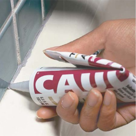 <b>Photo 4: Lay an even caulk bead</b></br> Pull the caulk tube down the tub/wall joint from the inside corner of the tub. Keep even pressure on the tube by pushing the caulk forward and folding over the empty portion.
