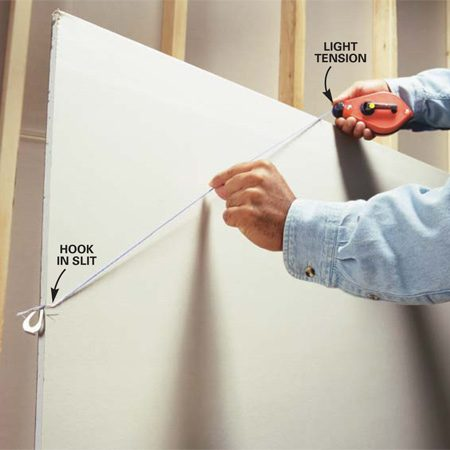 <b>Photo 4: Mark angle lines on drywall</b></br> Cut a slit in drywall with a utility knife and slip the string into it to secure the end. Cut the slit a little above the mark so the line will hit the mark when it's extended for an angle cut.