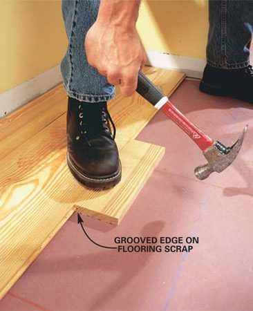 <b>Photo 6: Use a block to tap boards together </b></br> Fit the second board's groove onto the tongue of the first. Tap with a block (flooring scrap) and hammer to drive the boards together. For an antique look, create a small gap (1/16 in.) between the boards with a removable shim (see Photo 7).