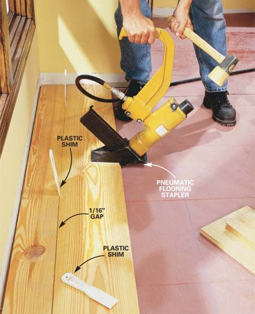 <b>Photo 7: Nail the floor every 2 ft. </b></br> Insert shims for even gaps, and nail through the tongue of the board with a flooring stapler. Start at one end of the board and work to the other, nailing every 2 ft.