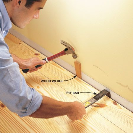 <b>Photo 16: Install the final board </b></br> Cut the final board to width and pry and wedge it into position (allow 1/4 in. between the board and the wall). You may have to put it in at an angle and tap it down. Face nail the board.